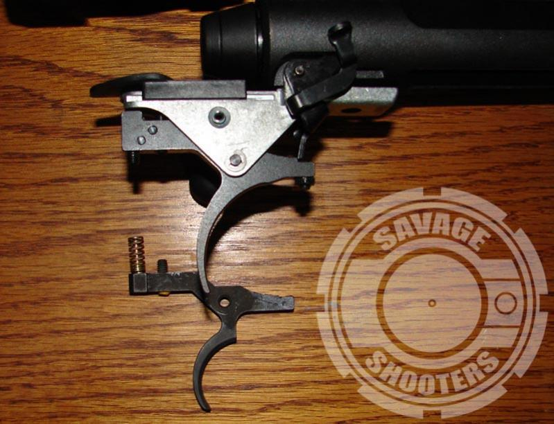 Timney replacement trigger in place on rifle, original trigger and spring on desk.